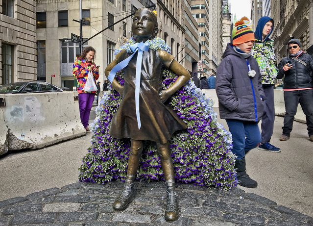 "Wall Street's ""Fearless Girl"" statue is draped with a bouquet of flowers to mark International Women's Day, Thursday March 8, 2018, in New York. The statue, which has been a New York City tourist attraction since it was installed to mark International Women's Day one year ago, is staying put for now while city officials figure out where it's going next to spread its message of female empowerment. (Photo by Karen Matthews/AP Photo)"