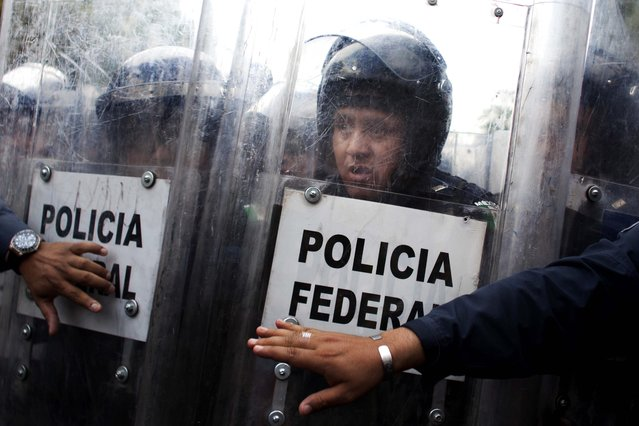 A Federal Police officer reacts while watching public school teachers breaking the fence that blocked a street near Mexico's Interior Ministry during a demonstration in Mexico City, on April 4, 2013. Many public school teachers are holding marches and blocking roads to battle a newly enacted education reform that would weaken union powers. (Photo by Alexandre Meneghini/Associated Press)
