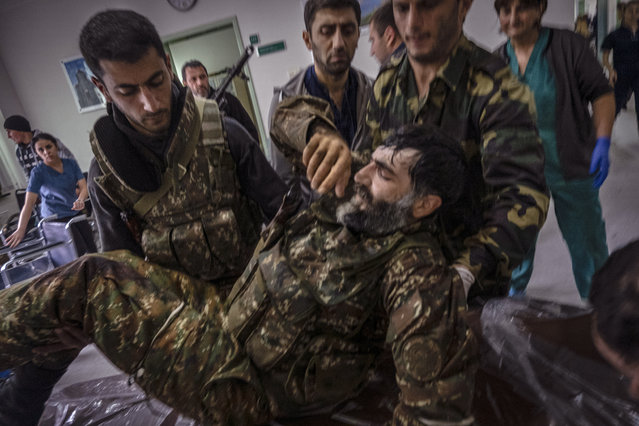 A soldier is taken into a hospital after being wounded at the front-line in the outskirts of Stepanakert, Nagorno-Karabakh, Friday, November 6, 2020. Nagorno-Karabakh authorities said that three civilians were killed by Azerbaijani shelling of the regional capital, Stepanakert on Friday. (Photo by Ricard Garcia Vilanova/AP Photo)