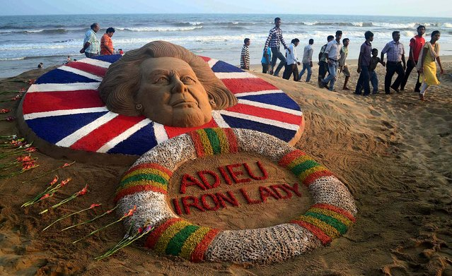 People walk past a sand sculpture of Margaret Thatcher, made by Sudarshan Pattnaik, in Puri, about 42 miles from the southeastern Indian temple city of Bhubaneswar, on April 9, 2013.  (Photo by Biswaranjan Rout/Associated Press)