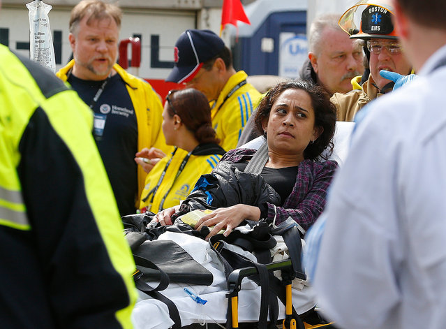 A woman is loaded into an ambulance after he was injured by one of two bombs exploded during the 117th Boston Marathon near Copley Square on April 15, 2013 in Boston, Massachusetts. (Photo by Jim Rogash)