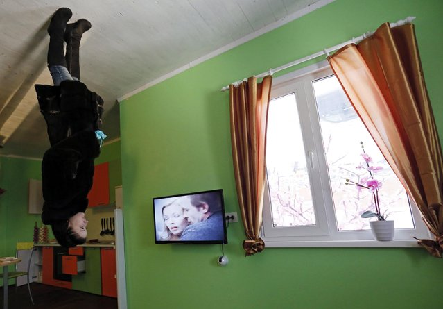 A woman visits a room in a house built upside-down in Russia's Siberian city of Krasnoyarsk, December 14, 2014. (Photo by Ilya Naymushin/Reuters)