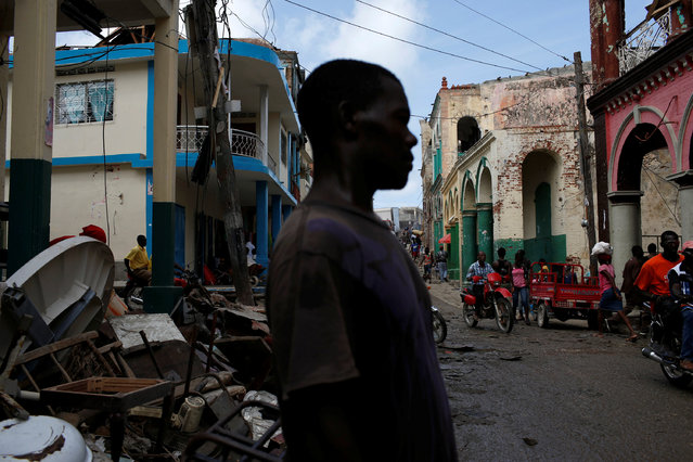 People walk down the street next to destroyed houses after Hurricane Matthew hit Jeremie, Haiti, October 10, 2016. (Photo by Carlos Garcia Rawlins/Reuters)