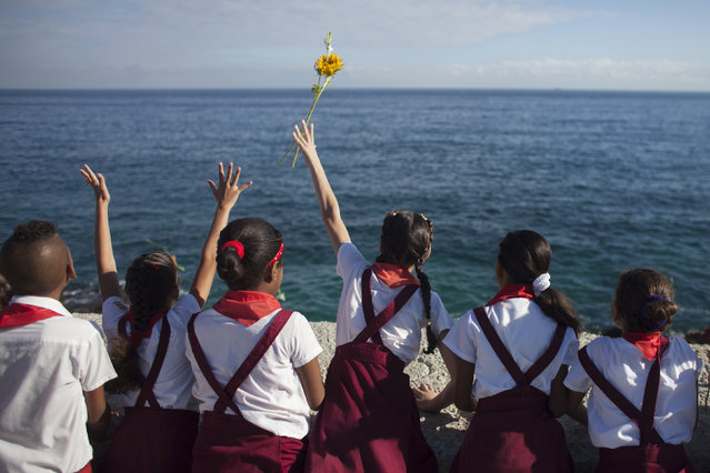 "Schoolchildren throw a flower into the sea in honor of rebel revolutionary commander Camilo Cienfuegos from Havana's seafront boulevard ""Malecon"" October 28, 2014. Cienfuegos was a commander of Fidel Castro's rebel army but died less than a year after their victory when his plane disappeared over the ocean on October 28, 1959 en route from Havana to Camaguey. The plane and his body were never found. (Photo by Alexandre Meneghini/Reuters)"