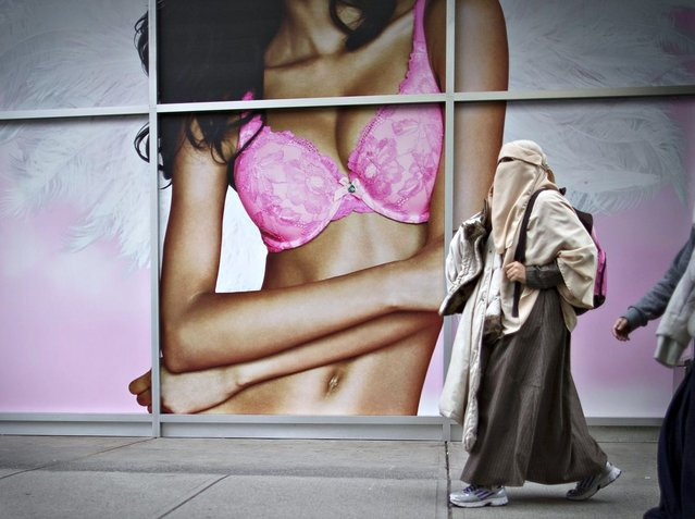 A Muslim woman wearing a hijab walks past a lingerie advertisement in downtown Vancouver, British Columbia April 26, 2013. (Photo by Andy Clark/Reuters)
