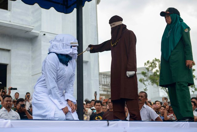 A woman is publicly flogged in front of a mosque in the provincial capital Banda Aceh on April 20, 2018. (Photo by Chaideer Mahyuddin/AFP Photo)