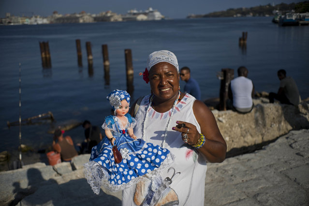 """In this April 13, 2018 photo, Santera Lourdes Nusa, 57, poses with her doll representing the Yoruba sea goddess """"Yemaya"""" in Regla, across the bay from Havana, Cuba. Lourdes became a self-employed Santera at a very young age, reading people's futures. """"The world is subject to change. Our country has always adopted a policy of improving relations with the entire world"""", she said, adding Donald Trump's position toward Cuba will not change Cuba's position to open relations with the U.S. (Photo by Ramon Espinosa/AP Photo)"""
