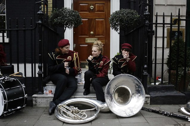 Musicians from The Spirit of South Paulding High School Band in Douglasville, Georgia in the U.S., eat a snack before the start of the New Year's Day Parade in London January 1, 2015. (Photo by Kevin Coombs/Reuters)