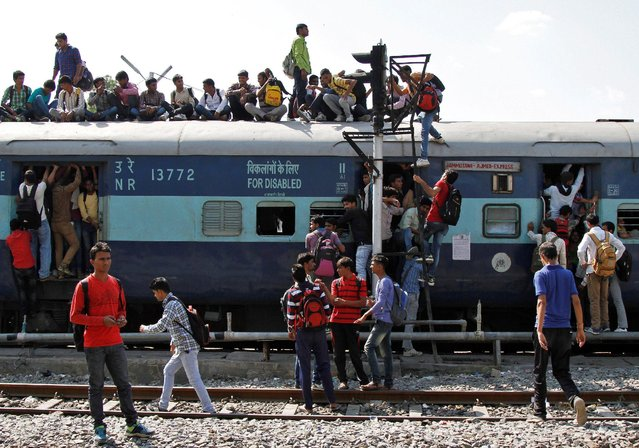 Passengers make use of a signal light pole to climb atop an overcrowded train at a railway station in Ajmer, India, October 23, 2016. (Photo by Himanshu Sharma/Reuters)
