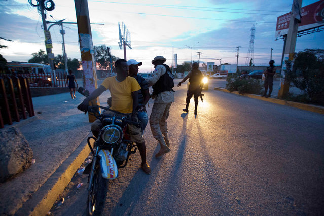 Police check motorists after a jail break at the Civil Prison in the coastal town of Arcahaiea, Haiti, Saturday, October 22, 2016. Over 100 inmates escaped after they overpowered guards who were escorting them to a bathing area. (Photo by Dieu Nalio Chery/AP Photo)