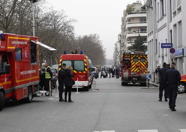 Policemen work at the scene after a shooting at the Paris offices of Charlie Hebdo January 7, 2015. (Photo by Youssef Boudlal/Reuters)