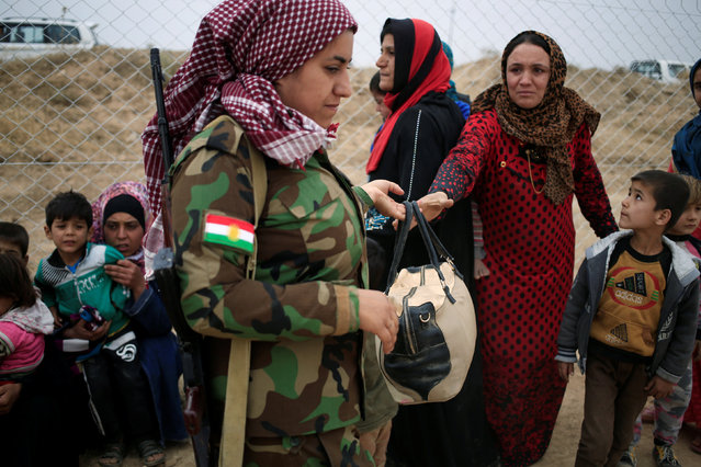 A Kurdish female Peshmerga soldier hands back a bag to a newly internally displaced woman upon her arrival at Al Khazar camp near Hassan Sham, east of Mosul, Iraq October 28, 2016. (Photo by Zohra Bensemra/Reuters)