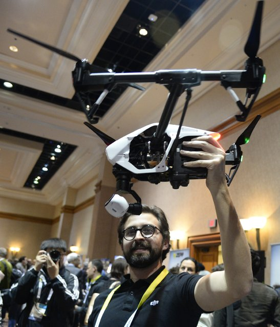 DJI representative Michael Perry displays the Inspire 1 quadcopter during a press event at the Mandalay Bay Convention Center for the 2015 International CES on January 4, 2015 in Las Vegas, Nevada. The quadcopter can fly up to 18 minutes and shoot up to 4K video and 12-megapixel still photos. It has carbon fiber arms that lower and lift automatically on take-off and landing and lift out of sight in flight to allow an unrestricted 360-degree view for the camera. (Photo by Robyn Beck/AFP Photo)