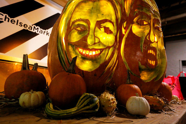 A giant pumpkin created by Master Carver Hugh McMahon with the faces of 2016 Democratic nominee Hillary Clinton and Republican presidential nominee Donald Trump is displayed at Chelsea Market in New York, U.S., October 28, 2016. (Photo by Eduardo Munoz/Reuters)