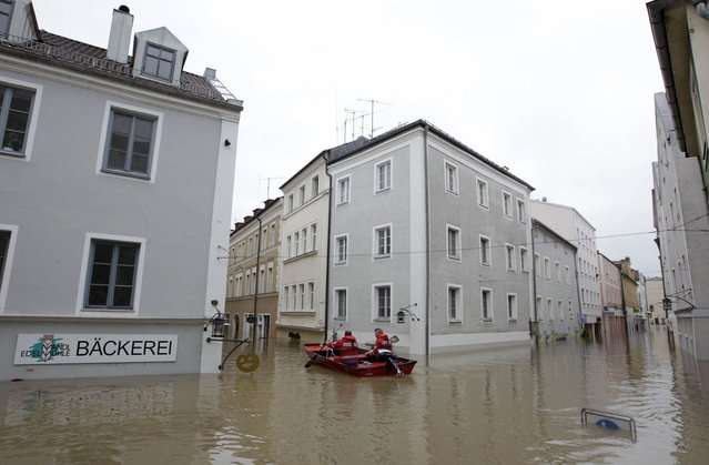 Members of the emergency services travel by boat along flooded streets in the centre of the Bavarian town of Passau, about 200 km (124 miles) north-east of Munich June 3, 2013. Torrential rain in the south and south-east of Germany caused heavy flooding over the weekend, forcing people to evacuate their homes. (Photo by Michaela Rehle/Reuters)