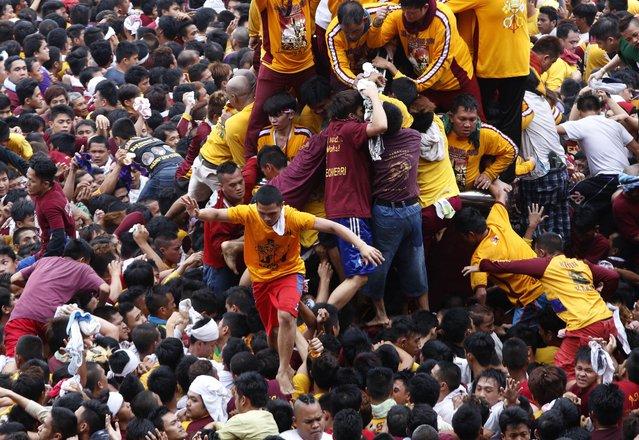 A devotee walks on the shoulders of people after kissing the Black Nazarene at the start of an annual procession in Manila, January 9, 2015. (Photo by Erik De Castro/Reuters)