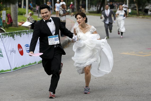 "Couples participate in the ""Running of the Brides"" race in a park in Bangkok, Thailand, November 28, 2015. (Photo by Athit Perawongmetha/Reuters)"