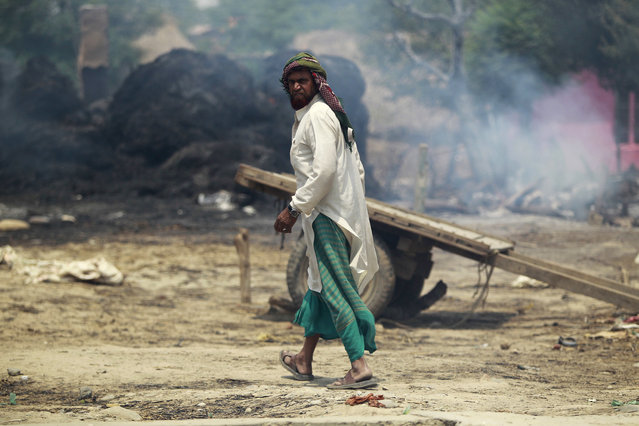 An Indian man walks near smoke rising from a residential area that was gutted from firing allegedly from the Pakistan side of the border in Jora farm village, in Ranbir Singh Pura district of Jammu and Kashmir, India, Tuesday, May 22, 2018. Villages along the India-Pakistan international border are almost deserted as most have moved to safer areas away from the volatile border region. (Photo by Channi Anand/AP Photo)