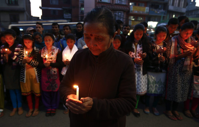 Anuradha Koirala, Chairperson of Maiti Nepal, a rehabilitation and orphanage home for HIV-affected children and women, attend a candlelight prayer meeting for those who have lost their lives due to HIV-Aids, on the eve of World AIDS Day in Kathmandu, Nepal, 30 November 2015. World AIDS Day is marked worldwide annually on 01 December to raise awareness for those living with the virus. (Photo by Narendra Shrestha/EPA)