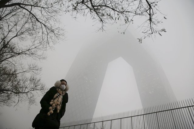 A woman wearing a protective mask walks in front of the China Central Television (CCTV) building on an extremely polluted morning as hazardous, choking smog continues to blanket Beijing December 1, 2015. (Photo by Damir Sagolj/Reuters)