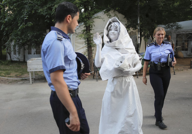 In this Thursday, May 24, 2018, photograph, an artist of Ukraine's Artel Myth, walks by Romanian police officers, before performing her Concordia character during the Living Statues International Festival, in Bucharest, Romania. Wait, did that statue really move? It may have been the question many themselves while taking a walk in Bucharest over the past week, during the International Living Statues Festival. (Photo by Vadim Ghirda/AP Photo)