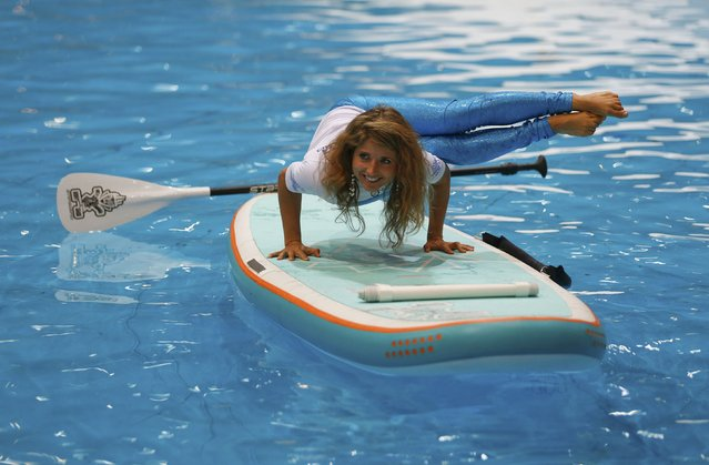 American Yoga teacher Dashama poses on a Yoga-board during a preview of the 46th International Boat Fair in Duesseldorf January 16, 2015. The BOOT 2015 watersports fair, with more than 1,600 international exhibitors will run in Duesseldorf from January 17 to January 25. (Photo by Ina Fassbender/Reuters)