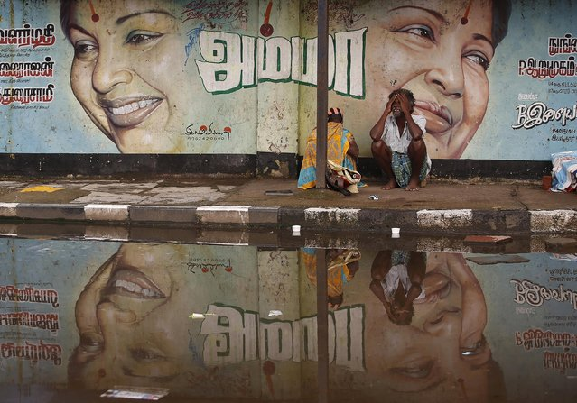 A flood-affected couple sits along a flooded roadside under a picture of Jayalalithaa Jayaram, chief minister of the southern Indian state of Tamil Nadu, in Chennai, India, December 6, 2015. (Photo by Anindito Mukherjee/Reuters)
