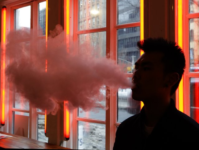 In this February 20, 2014 file photo, a man exhales vapor from an e-cigarette in New York. Using certain electronic cigarettes at high temperature settings could release much more formaldehyde, a cancer-causing chemical, than smoking traditional cigarettes does, lab tests suggest. The research published in the New England Journal of Medicine on Wednesday, January 21, 2015. (Photo by Frank Franklin II/AP Photo)