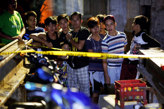 People gather behind police line at the site where a man was killed by two motorcycle-riding gunmen in Manila, Philippines early October 29, 2016. (Photo by Damir Sagolj/Reuters)