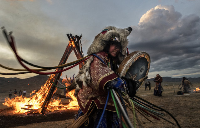 A Mongolian Shamaness or Buu, beats her drum while taking part with others in a fire ritual meant to summon spirits to mark the period of the Summer Solstice in the grasslands on June 22, 2018 outside Ulaanbaatar, Mongolia. (Photo by Kevin Frayer/Getty Images)