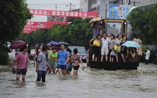 Residents are evacuated through a flooded street by an excavator in Guanghan city in southwestern China's Sichuan province Tuesday July 9, 2013. (Photo by AP Photo)