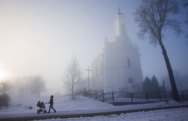 A woman pushes a pram with a child as heavy fog covered streets in a small town of Zaslavl, northwest of Minsk, December 10, 2014. (Photo by Vasily Fedosenko/Reuters)