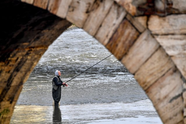 A fisherman is fishing in river Vardar in Skopje, North Macedonia, 22 December 2020. Following a meeting with Bulgarian officials, Macedonian health minister Filce announced that Bulgaria will also donate to North Macedonia from every shipment of COVID-19 vaccines which they bought directly from the producers. (Photo by Georgi Licovski/EPA/EFE)