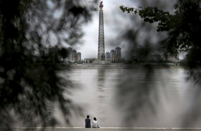A North Korean couple sits by a river with a view of Ju Che Tower from Kim Il Sung Square on Sunday, July 21, 2013, downtown Pyongyang, North Korea. (Photo by Wong Maye-E/AP Photo)