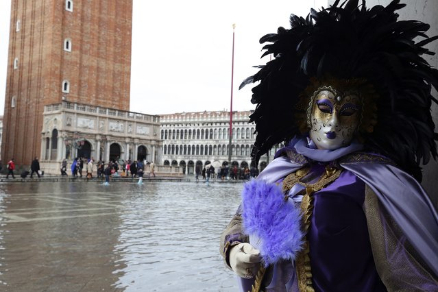 A masked reveller poses along the flooded St. Mark's Square during a period of seasonal high water and on the first day of carnival, in Venice February 1, 2015. (Photo by Stefano Rellandini/Reuters)
