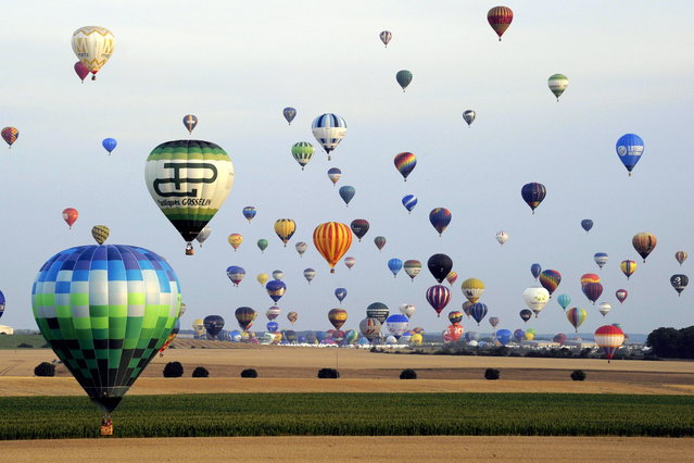 "Hot-air balloons take off in Chambley-Bussieres, eastern France, on Saturday July 27, 2013 in an attempt to set a world record for collective taking-off during the event ""Lorraine Mondial air ballons"", an international hot-air balloon meeting. (Photo by Alexandre Marchi/AP Photo/L'est Republicain)"