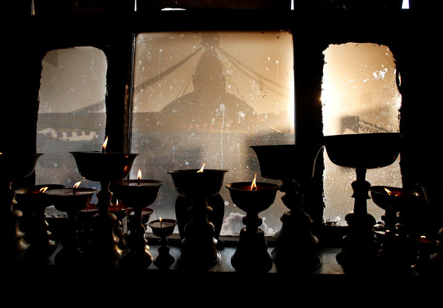 Boudhanath Stupa is seen through a window as butter lamps are offered during the opening of the stupa, which underwent renovation after suffering damage during the 2015 earthquake, in Kathmandu, Nepal November 22, 2016. (Photo by Navesh Chitrakar/Reuters)
