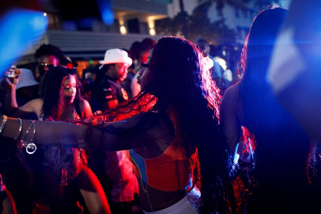 People enjoy spring break festivities ahead of an 8pm curfew imposed by local authorities, amid the coronavirus disease (COVID-19) outbreak in Miami Beach, Florida, U.S., March 20, 2021. (Photo by Marco Bello/Reuters)