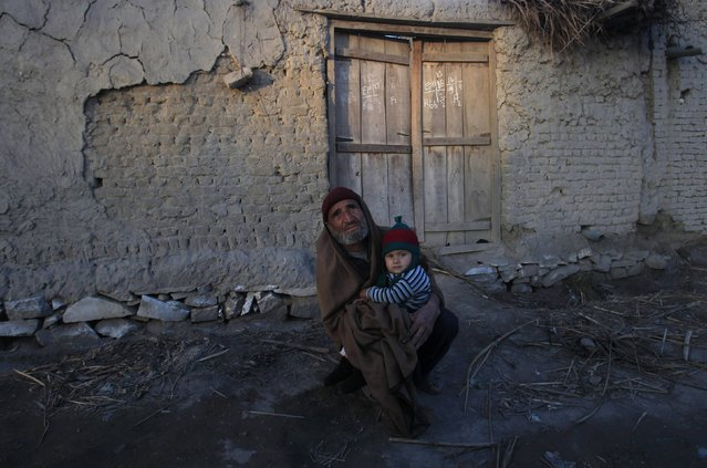 A man and his grandson wear warm clothing to beat the cold weather while sitting outside his home in Charsadda, near Peshawar January 27, 2015. (Photo by Fayaz Aziz/Reuters)