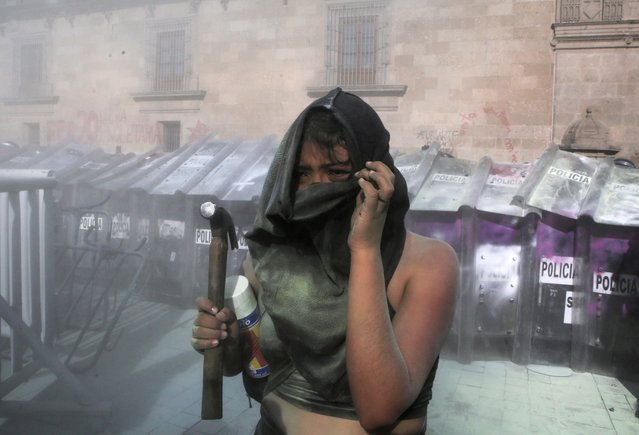 A woman reacts while holding a hammer during a protest in support of Victoria Salazar, a Salvadoran woman who died after a Mexican female police officer was seen in a video kneeling on her back, in Mexico City, Mexico on April 2, 2021. (Photo by Raquel Cunha/Reuters)