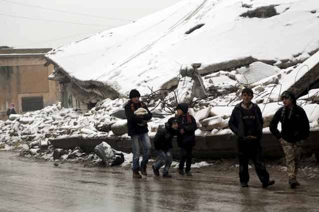 Boys walk past damaged buildings covered with snow in the rebel-controlled area of Maaret al-Numan town in Idlib province, Syria, January 5, 2016. (Photo by Khalil Ashawi/Reuters)