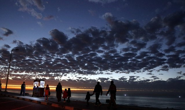 A Palestinian family walks on the beach road in Gaza City, Thursday January 07, 2016. (Photo by Hatem Moussa/AP Photo)