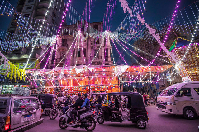 Vehicles, motorcycles, and tuk-tuks (motorised rickshaws) drive past a stall selling Ramadan lanterns along a main street in the in the northern suburb of Shubra (home to a large Christian population) of Egypt's capital Cairo on April 12, 2021, at the start of the Muslim holy fasting month of Ramadan. (Photo by Khaled Desouki/AFP Photo)