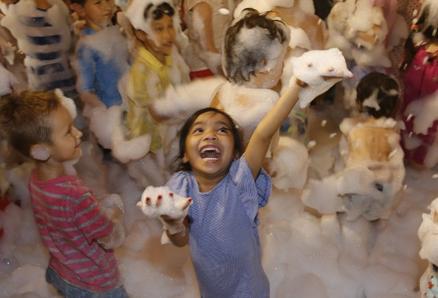 Children play in a fake snowfall of foam at a Christmas tree outside a mall near Orchard Road in Singapore December 5, 2014. (Photo by Edgar Su/Reuters)