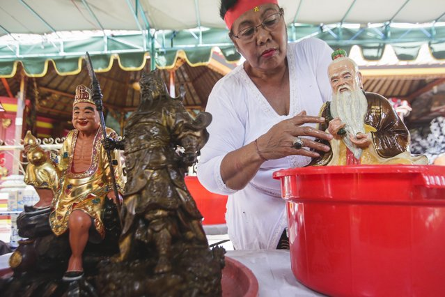 A Balinese woman cleans a statue during preparations for the upcoming Chinese New Year at a temple in Denpasar, Bali, Indonesia, 12 February 2015. (Photo by Made Nagi/EPA)