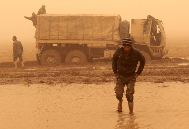 Iraqi army soldiers attempt to move their truck stuck in the mud near the village of Al-Boutha al-Sharqiyah, west of Mosul, on December 2, 2016, during a broad offencive by Iraq forces to retake the main hub city from Islamic State group jihadists. (Photo by Ahmad Al-Rubaye/AFP Photo)