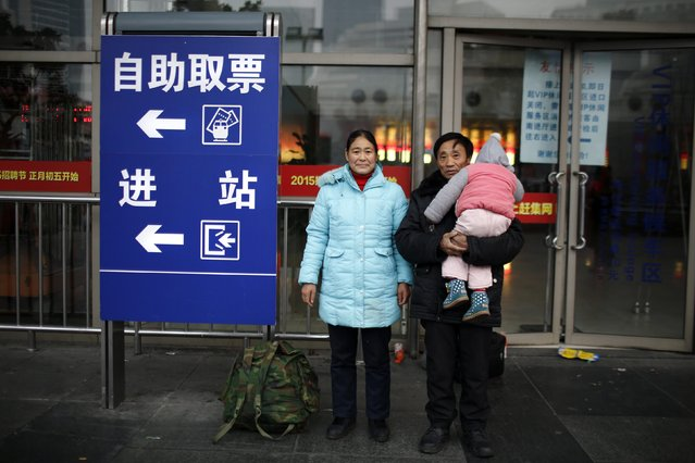 He Chengsan carries his grandson next to his wife Feng Guiyin as they pose for a portrait at the Shanghai railway station February 12, 2015. He and Feng travelled from Chengdu on a train to spend Chinese New Year with their daughter in Shanghai. (Photo by Carlos Barria/Reuters)