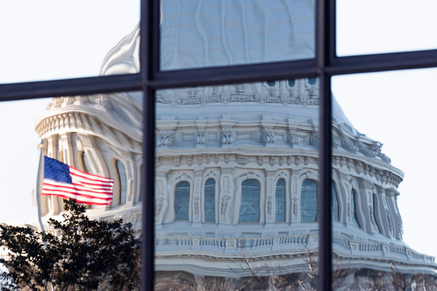 The image of the US Capitol Building is seen reflected in glass windows in Washington, DC, USA, 08 December 2020. Lawmakers are set to extend a deadline by one week to prevent a partial government shutdown as a temporary spending bill is set to expire on 11 December. (Photo by Michael Reynolds/EPA/EFE)
