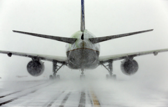 A United Airlines jet blows snow on a runway at O'Hare International Airport, Sunday, February 1, 2015, in Chicago. More than 1,100 flights have been canceled at Chicago's airports and snow-covered roads are making travel treacherous. (Photo by Nam Y. Huh/AP Photo)