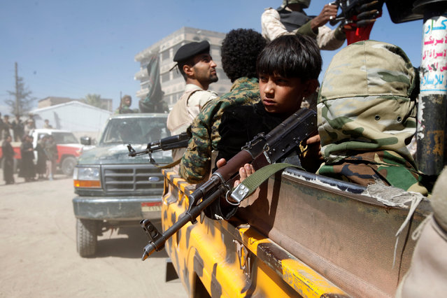 A boy holds his weapon as he sits with armed tribesmen loyal to the Houthi movement riding a truck during a rally held to mobilize fighters for the battles against government forces, in Sanaa, Yemen December 1, 2016. (Photo by Mohamed al-Sayaghi/Reuters)